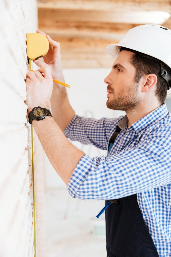 Close-up portrait of builder measuring something with yellow type